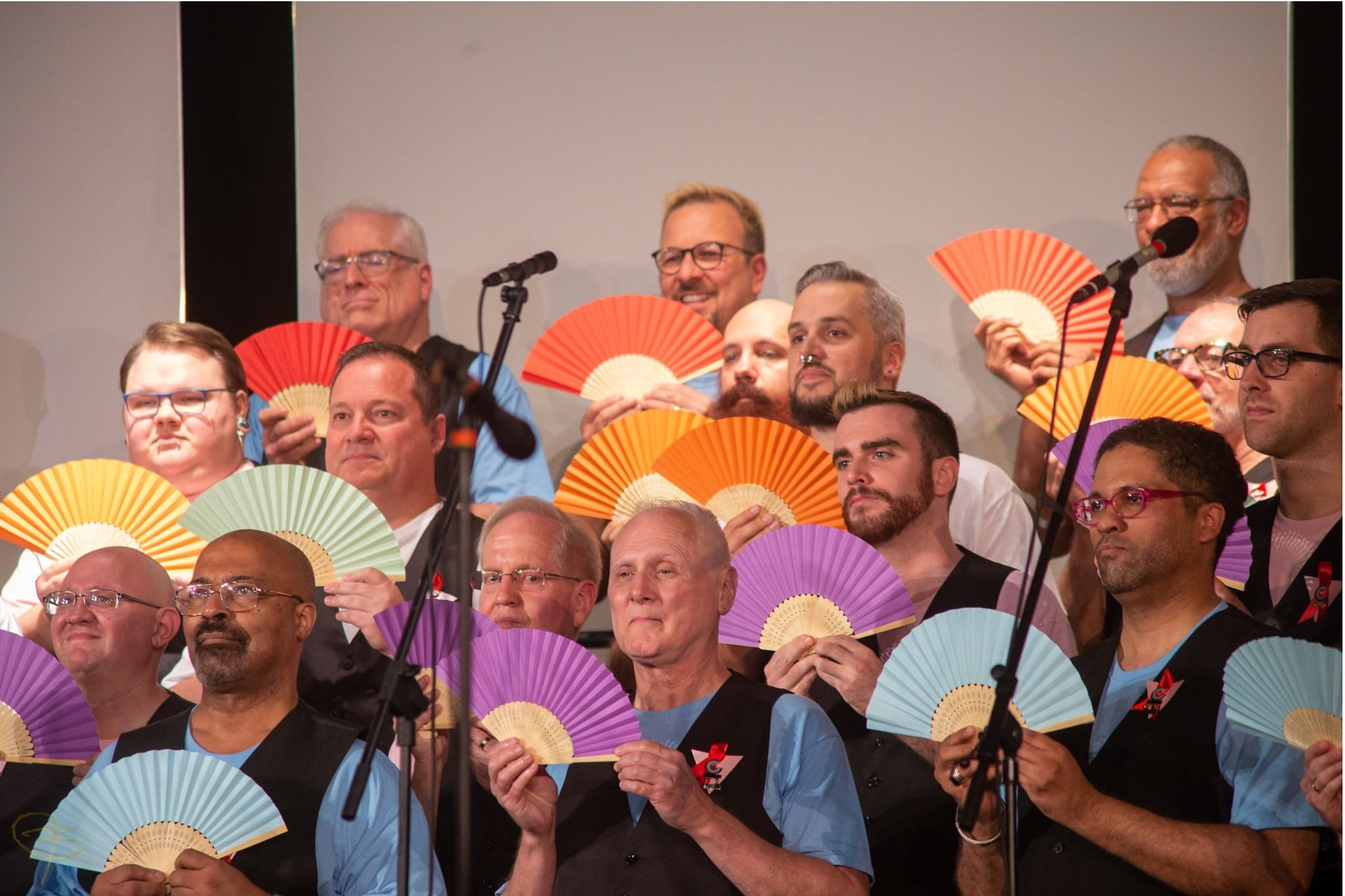Image of members of the Cincinnati Men's Chorus, on stage, with multicolor paper fans